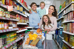 Clienti positivi con i bambini che comprano alimento nell'ipermercato Immagini Stock