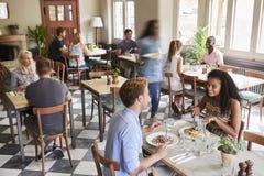 Clients appréciant des repas dans le restaurant occupé photo stock