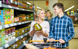 Clients buying tinned food. Smiling clients buying tinned food at grocery shop royalty free stock photos