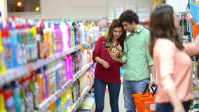 Clients choisissant des produits d'entretien dans le supermarché banque de vidéos