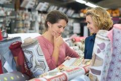 Clients d'amis choisissant le tapis dans l'hypermarché d'articles de ménage image libre de droits