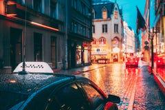 Clients d'attente de voiture de taxi dans de vieilles rues européennes dans la soirée pluvieuse Illuminations de rue de nuit images libres de droits