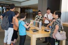 Clients dans le magasin d'Apple Photographie stock