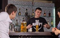 Clients de portion de barman au compteur de barre Photos stock