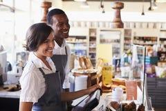 Clients de portion de personnel au contrôle d'épicerie fine photo stock
