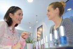 Clients féminins de portrait faisant des emplettes dans le magasin de beauté Photographie stock libre de droits
