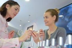 Clients féminins de portrait faisant des emplettes dans le magasin de beauté Images libres de droits