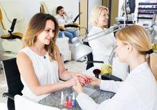Clients féminins faisant des clous dans le salon de clou dans l'après-midi photographie stock libre de droits