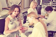 Clients féminins faisant des clous dans le salon de clou dans l'après-midi photo stock