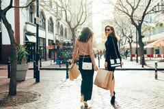 Clients féminins marchant sur la rue de ville avec des paniers Photos stock