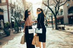Clients féminins portant des paniers sur la rue de ville Images stock