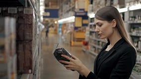 Clients heureux de femme choisissant le thé noir de stock de nourriture, femmes de brune dans le supermarché, faisant des emplett Photo stock