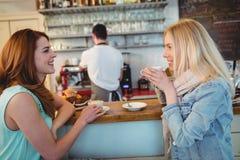 Clients heureux parlant au compteur dans le café photo stock