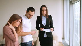 Clients meeting with estate agent, flat viewing, renting buying apartment. Female real estate agent showing flat to clients, telling about advantages, property stock video footage