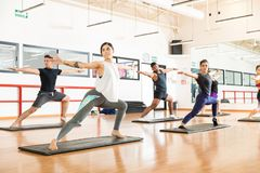 Clients Performing Warrior Pose Ii On In Health Club royalty free stock photography