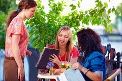 Clients polis de portion de serveuse sur la terrasse de café d'été Image stock