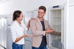 Clients regardant des réfrigérateurs dans le magasin d'électro-ménagers Photographie stock