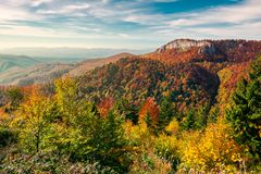 Cliff above the forest in fall color. Beautiful landscape in mountains of Romania. cliff above the forest in fall color. beautiful view in evening light with stock images