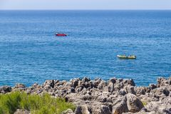 Cliff, boat and ocean in Cascais Royalty Free Stock Photography