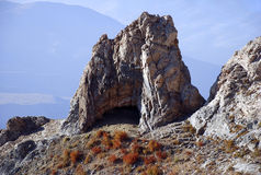 Cliff with a cave in the mountains of Tien Shan Stock Image