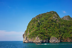 Cliff and the clear sea with long-tail near Phi Phi island in so stock photography