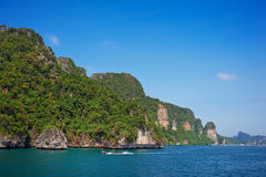 Cliff and the clear sea with long-tail near Phi Phi island in south Thailand Royalty Free Stock Photo