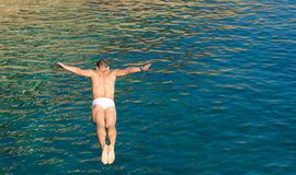 Cliff diver guy jumping in the blue sea from high rocks wall royalty free stock photos