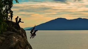 Cliff diving at Kande Beach, Nkhata Bay, Lake Malawi, Malawi. Cliff diving against a golden sunset at Kande Beach, Nkhata Bay, Lake Malawi, Malawi royalty free stock image