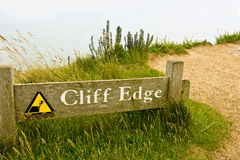 Cliff Edge. A wooden warning sign on a cliff edge at Beachy Head Stock Photos