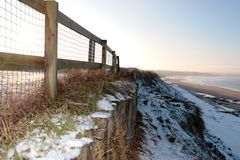 Cliff edge fence over beach Royalty Free Stock Photo