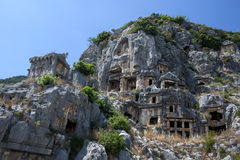 A  cliff face covered in Lycian rock-cut tombs at the ancient site of Myra at Demre in Turkey. Stock Photos