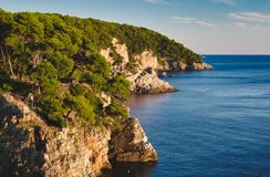 Cliff face with forest trees on a Mediterranean island. With blue sea and sky stock photo
