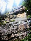 Cliff face lit up. Sunshine rays peek out of top the cliff and light up its vast face of rocks and trees royalty free stock photography