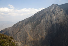 Cliff Face in Tiger Leaping Gorge. A towering cliff face of sheer stone stretches deep into Tiger Leaping Gorge in Yunnan province in China stock image