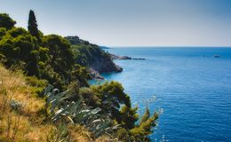 Cliff face with trees, plants and dried grass on a Mediterranean island. With blue sea and sky royalty free stock photo