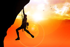 Cliff Hanger. Silhouette illustration of a man figure hanging on the cliff Stock Photo