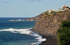 Cliff hugging waterfront homes. Cling to to the edge, overlooking the black sand beach below of Fonti di Billa, as waves crash Stock Photo