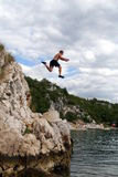 Cliff Jumping. A young man jumps from a cliff into the sea Royalty Free Stock Images