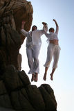 Cliff jumping. Couple jumping together from the top of the mountain Stock Photography