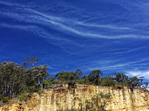 Cliff landscape by rich blue sky with cirrus clouds Royalty Free Stock Images