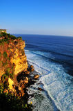 Cliff near the sea under sunset. A cliff near the ocean, with waves hitting it Royalty Free Stock Image