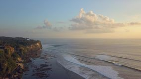 Cliff next to the ocean. Tall cliff next to the blue ocean with big waves in bali indonesia stock video