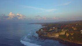 Cliff next to the ocean. Tall cliff next to the blue ocean with big waves in bali indonesia stock video footage