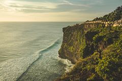 Cliff, ocean shore, tourist path. Panorama. Bali. Cliff, ocean shore, tourist path. Panorama. Uluwatu. Bali island. Indonesia. Stunning scenery the high green royalty free stock image