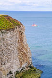 Cliff off Flamborough Head with boat. Steep cliff off Flamborough Head with distant boat Stock Images
