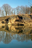 Cliff at a pond with reflection. Rock landscape at the shore of a lake in the spring Stock Photo