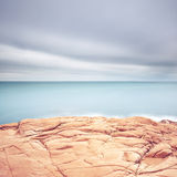 Cliff rocks, blue ocean and cloudy sky background. Royalty Free Stock Photos