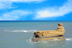 Cliff in sea against blue sky Royalty Free Stock Photography