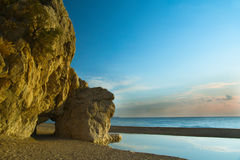 Cliff on sea coast, with copyspace. Yellow cliff on sea shore in the backdrop of clear sky with sparse clouds Royalty Free Stock Image