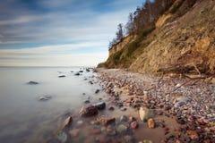 Cliff on sea shore at sunrise. Baltic sea long exposure photo Stock Photo